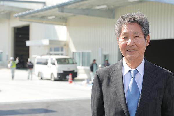 新工場前でインタビューに応じる竹田様