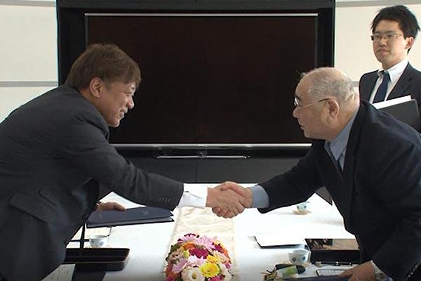 契約書に調印し固く握手を交わす五十嵐社長(右)と谷口社長(左)